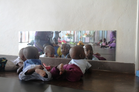 Babies look at their reflection during play time at the babies home in Suubi. Almost 100 orphans live at the Suubie babies home.