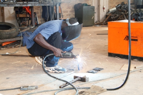 A member of Watoto's fabrication unit welds part of a picnic table. The fabrication unit builds much of the furniture for the children villages and babies homes.