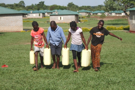 Four Watoto children work together to move jugs of water up a hill.