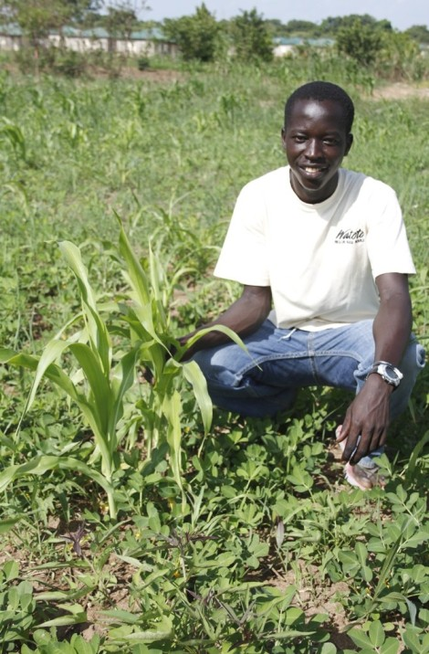 Watoto student, George, kneels near one of his corn plants on a sunny Ugandan afternoon. The 17 year old, who is a former child soldier, has a true passion for agriculture.