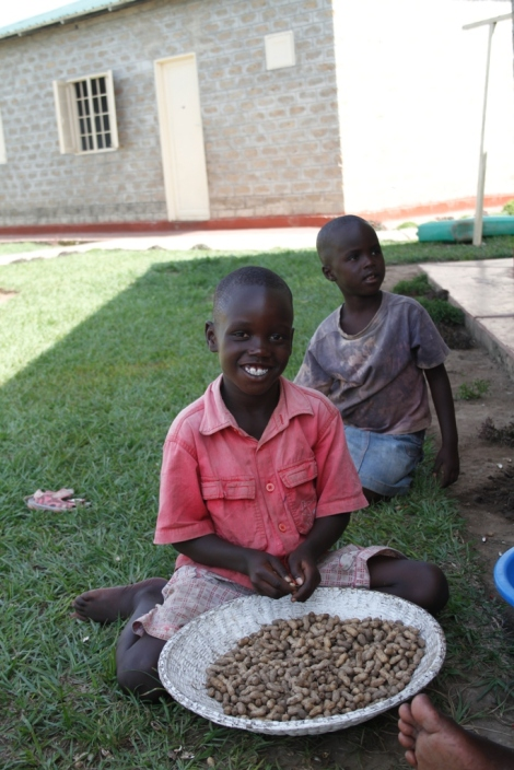 A little boy helps his house mother shell peanuts. Each home in the Watoto children's villages house eight children under the care of a house mother.